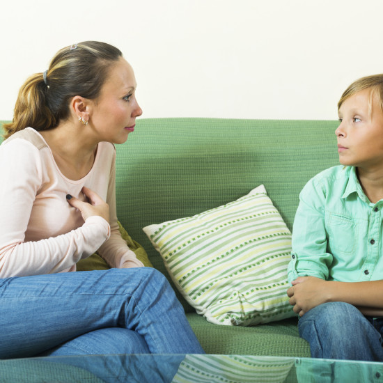 teenager son and mother having serious talking on sofa in home